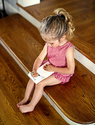 Little girl sitting on step writing on paper - p3721207 by Abigail Pope