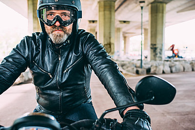 Mature male motorcyclist wearing black helmet and goggles sitting on motorcycle under flyover - p429m1175063 by Eugenio Marongiu