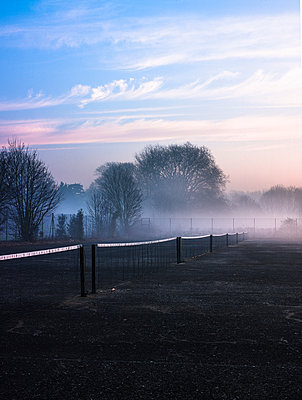 Row of tennis nets in misty park at sunrise - p429m1418138 by David Cleveland