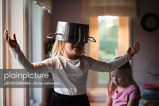 Girl wearing pot on head - p312m2086464 by Anna Johnsson