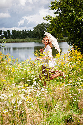 Blonde woman running through flowering meadow - p1093m2193606 by Sven Hagolani