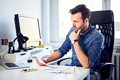 Man reading document at desk in office - p300m1567748 by Bartek Szewczyk