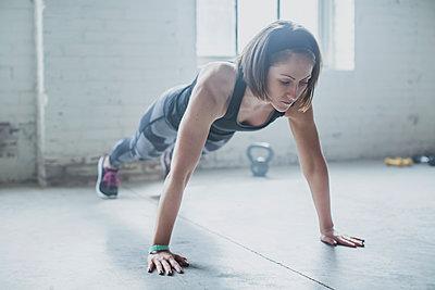 Athlete doing push-ups in gym - p555m1411971 by John Fedele