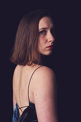 Woman in the dark turning around - p1323m2064035 von Sarah Toure