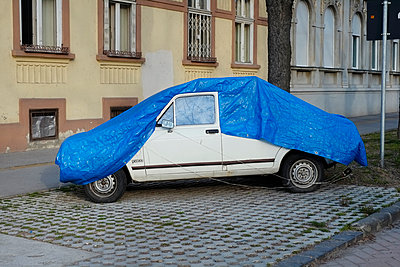 Old white car covered with a blue plastic cover  - p1527m2116785 by Slaveng