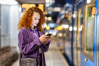 Curly haired woman using mobile phone at tram station - p300m2293969 by William Perugini