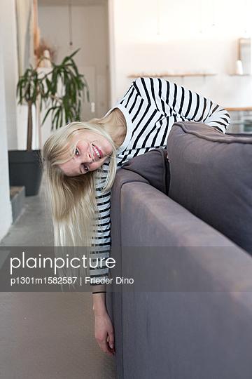 Junge Frau ist entspannt auf dem Sofa - p1301m1582587 von Delia Baum