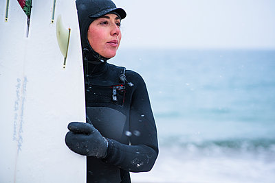 Young woman going winter surfing in snow - p1166m2177044 by Cavan Images