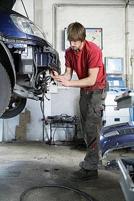 Germany, Ebenhausen, Mechatronic technician working in car garage - p30020016f by Tom Chance