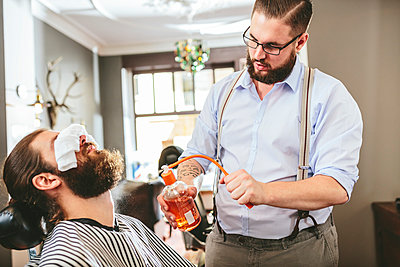 Barber spraying aftershave on beard of a customer - p300m1052981f by Matthias Drobeck