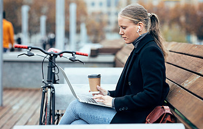 Woman in trench coat using laptop while sitting on bench by bicycle - p300m2256042 by Josep Suria