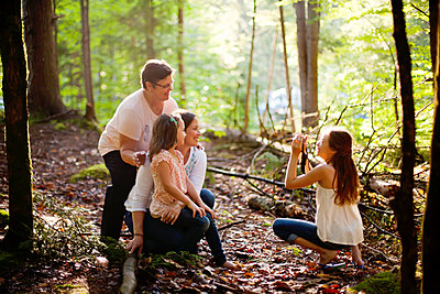 Caucasian girl photographing family in forest - p555m1409463 by Shestock
