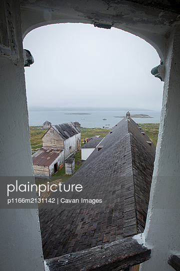 View of ocean and abandoned buildings from window in Torngats Mountains National Park - p1166m2131142 by Cavan Images