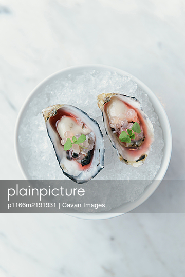Oyster halves on a bed of ice at gastronomic restaurant - p1166m2191931 by Cavan Images