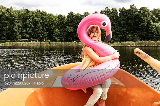 Girl with flamingo swimming ring in rowing boat - p294m2206287 by Paolo