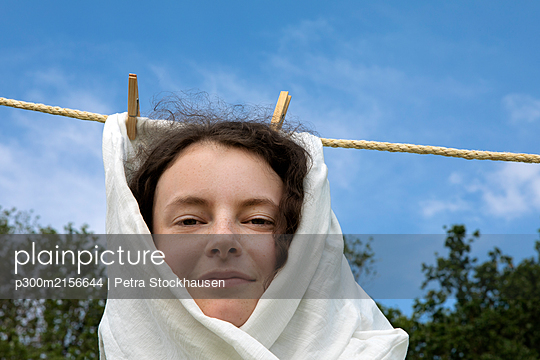 Portrait of smiling young woman wrapped in white cloth haning on clothesline - p300m2156644 von Petra Stockhausen