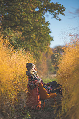 Pregnant woman sitting on chair in asparagus field in autumn - p300m2068997 by Anke Scheibe