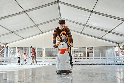 Grandfather and grandson on the ice rink, ice skating, using ice bear figure as prop - p300m2077791 by Zeljko Dangubic