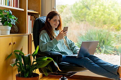 Smiling woman with laptop using smart phone while sitting on chair at home - p300m2264473 by VITTA GALLERY