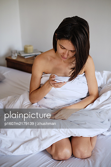 Young woman sitting in her bed with smartphone - p1607m2179139 by zhushman