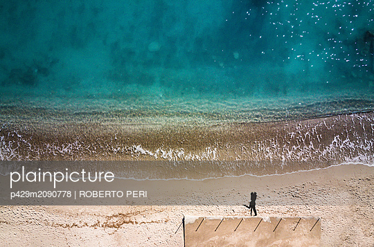 Couple hugging on beach - p429m2090778 by ROBERTO PERI