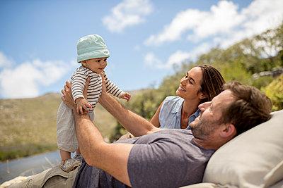 Familie mit Baby entspannt sich am Seeufer - p1355m1574052 von Tomasrodriguez