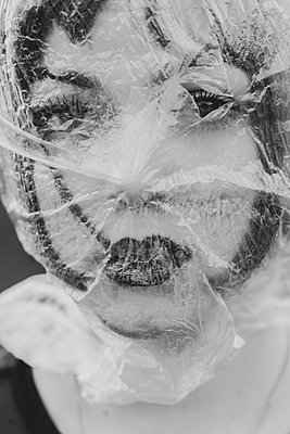 Junge Frau mit einer Folie vor dem Gesicht - p1564m2142564 von wpsteinheisser