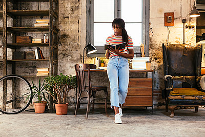 Young woman standing in front of desk in a loft using notebook - p300m1580985 by Bonninstudio