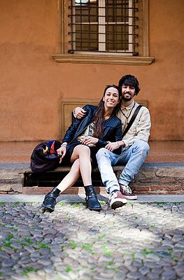 Portrait of happy young couple sitting on steps outdoors - p300m2059990 von Giorgio Fochesato