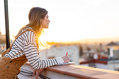 Young woman taking notes on roof terrace at sunset - p300m2083057 by VITTA GALLERY