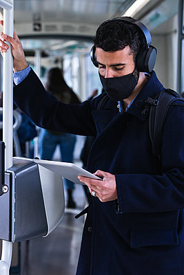 Businessman wearing protective face mask using digital tablet while standing in train - p300m2267133 by NOVELLIMAGE