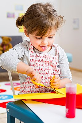 Girl cutting coloured card at home - p429m1024459f by Emely