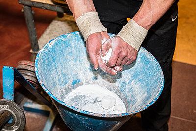 Sportler reibt Hände mit Talkum ein - p930m1200522 von Phillip Gätz