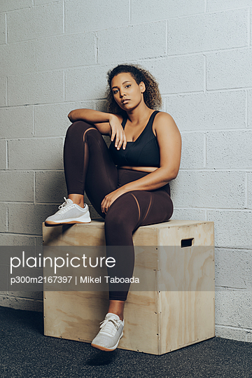Portrait of confident athletic young woman sitting on a box - p300m2167397 by Mikel Taboada