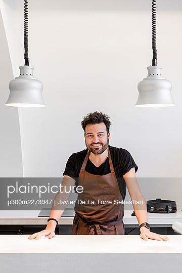 Smiling expertise standing by kitchen island in modern restaurant - p300m2273947 by Javier De La Torre Sebastian