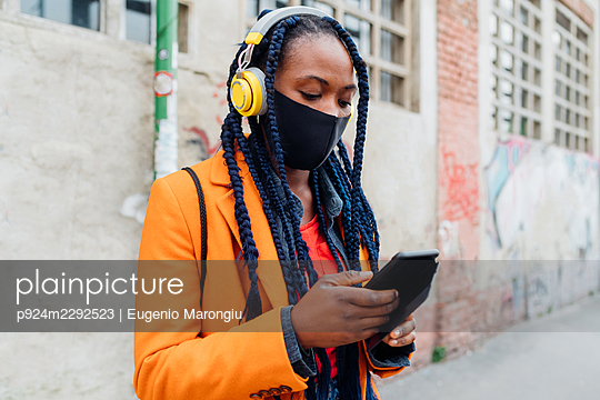 Italy, Milan, Woman with headphones and face mask holding smart phone - p924m2292523 by Eugenio Marongiu