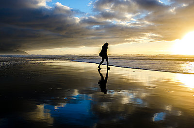 Silhouette woman walking at beach against cloudy sky during sunset - p1166m1534149 by Cavan Social