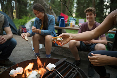 Teenage outdoor school students toasting marshmallows, making smores at campsite campfire - p1192m1490922 by Hero Images