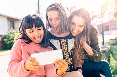 Three playful girls taking a selfie outdoors - p300m1469784 by Marco Govel