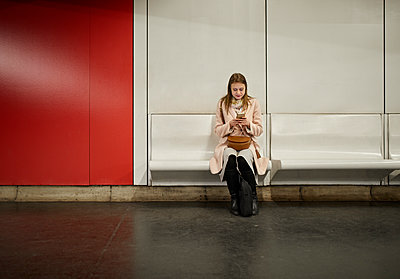 Austria, Vienna, young woman waiting at underground station using smartphone - p300m2084081 by Zeljko Dangubic