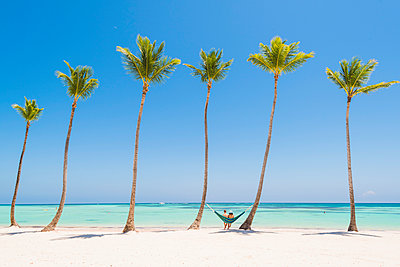 Juanillo Beach (playa Juanillo), Punta Cana, Dominican Republic. Couple relaxing on a hammock on a palm-fringed beach (MR). - p651m2006848 by Marco Bottigelli