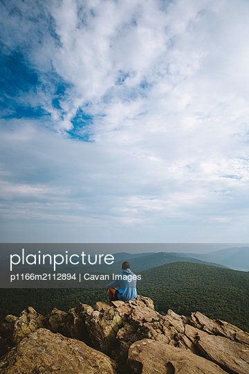 A young adult sits on a cliff overlooking a wide mountain range in VA. - p1166m2112894 by Cavan Images