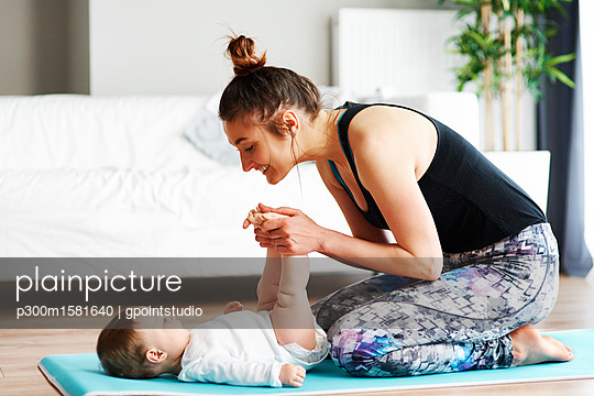 Mother with baby exercising on yoga mat at home - p300m1581640 von gpointstudio