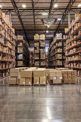 View down aisles of racks holding cardboard boxes of product on pallets  in a large distribution warehouse - p1100m1575463 by Mint Images