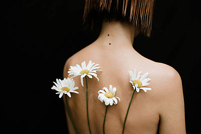 Naked woman with chamomiles on her back against black background - p1166m2111993 by Cavan Images