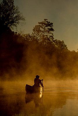 Sunrise canoe ride on foggy river. - p1166m2269647 by Cavan Images