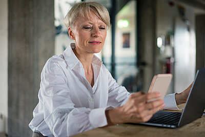 Blond businesswoman with laptop using mobile phone while sitting at desk in home office - p300m2267803 by Robijn Page