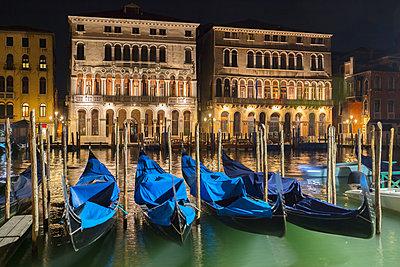 Gondolas on Grand canal waterfront at night, Venice, Veneto, Italy - p429m2051028 by Fabio Muzzi