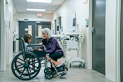 Smiling doctor comforting girl in wheelchair - p555m1521449 by FS Productions