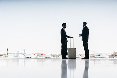 Two businessmen on airfield - p586m1208571 by Kniel Synnatzschke